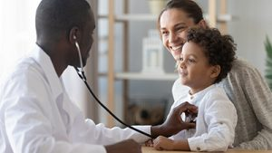 African male pediatrician hold stethoscope exam child boy patient visit doctor with mother, black paediatrician check heart lungs of kid do pediatric checkup in hospital children medical care concept