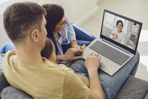 Online medical consultation for family patients. Doctor woman video call using laptop talks with family sitting on the sofa at home. Telemedicine concept virtual hospital medicine diagnosis symptoms prescription for patients.